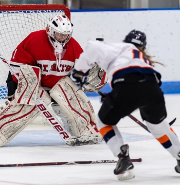 St. Paul's goalie Madison Beck has a Milton forward bearing down on her.