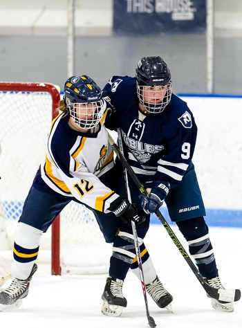 BB&N's Kayla Dunn (12) and Nobles' Abby Volo (9) battle for net-front position in Nobles' 4-0 win at the Harrington Tournament Saturday morning.